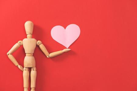 Hölzerne Mannzahl, die rotes Herz hält. Konzept zum Valentinstag.