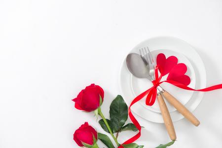 Festliches Gedeck mit Tischbesteck, wenig Rose und Herzen auf rosa Tabelle Standard-Bild - 94880385