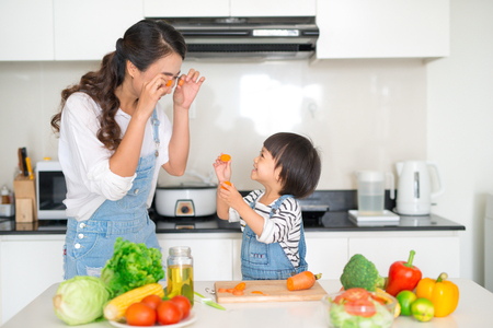 Mother with her daughter in the kitchen cooking together