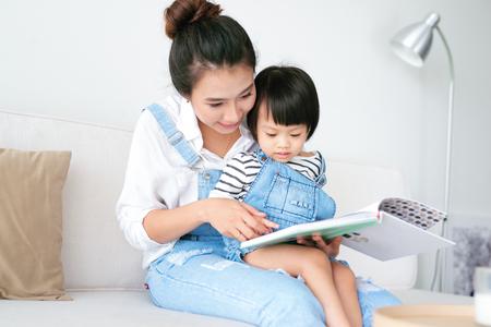 幸せな愛情の家族。かわいいアジアの母親が娘に本を読む