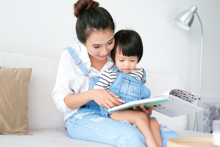 Happy loving family. Pretty young asian mother reading a book to her daughter Standard-Bild