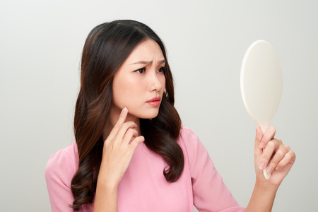 Asian woman looking at the mirror with the trouble on her skin.