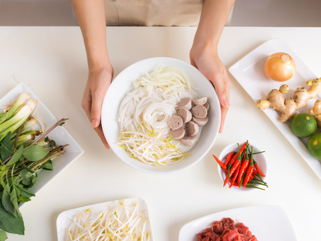 Female chef prepare traditional Vietnamese soup Pho bo with herbs, meat, rice noodles Stok Fotoğraf - 95078490