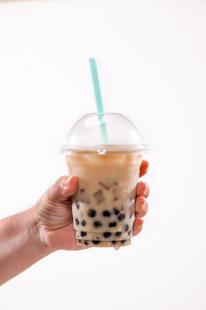 Holding a plastic glass of refreshing Taiwan iced milk tea with bubble (boba)