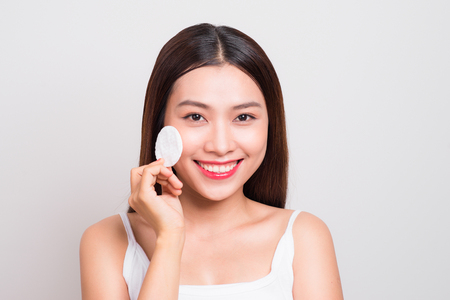 Happy smiling beautiful young asian woman cleaning skin by cotton pad. Banco de Imagens