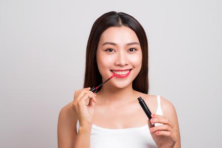 뷰티 메이크업. 립글로스를 적용하는 젊은 아시아 여성 스톡 콘텐츠