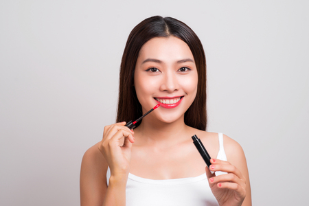 Beauty makeup. Young asian woman applying lip gloss