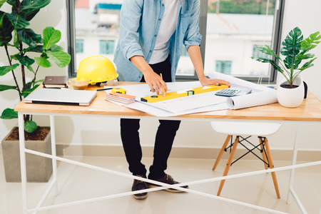 Engineer or architect in blue pullover is working on construction plans. Фото со стока