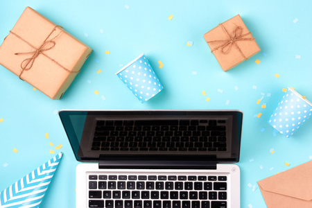 Gift box, birthday party things and laptop on a blue background Stock Photo