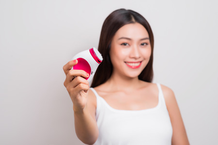 Young asian woman uses an electric brush for deeply clean