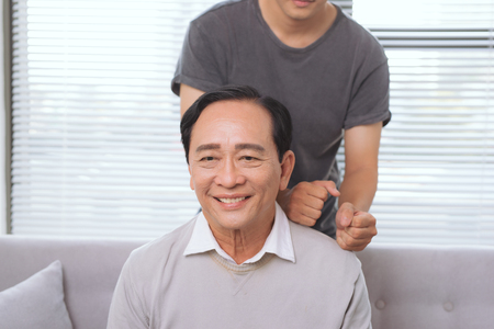 Son massaging father shoulder, sitting on sofa.