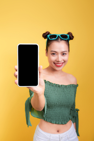 Portrait of a cheerful cute woman showing blank smartphone screen isolated over yellow background Archivio Fotografico