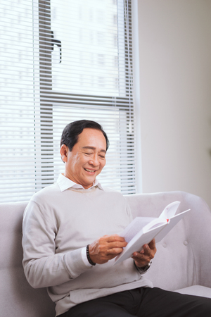 Portrait of an happy mature man reading a book relaxed at home.