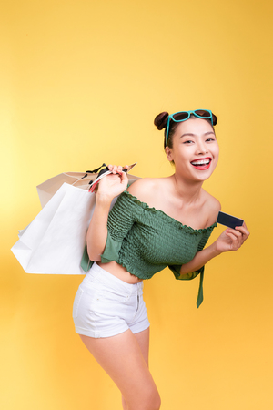 Shopping asian woman holds shopping bags and a credit card on yellow background Archivio Fotografico