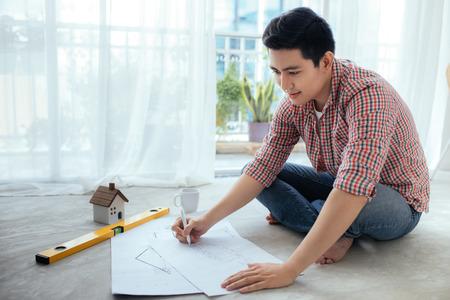 Jonge knappe mannelijke Aziatische architect die thuis aan de vloer werkt. Stockfoto