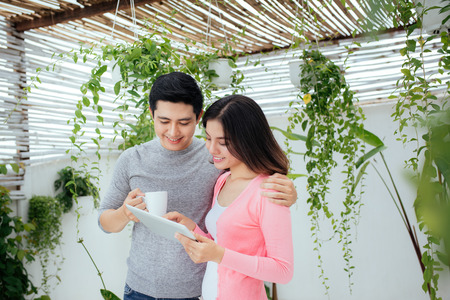 Love couple at home.  Young asian relaxing on a balcony's garden. Stock Photo - 95638251