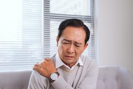 Älterer Mann leidet unter Schulterschmerzen sitzen auf einem Sofa im Wohnzimmer