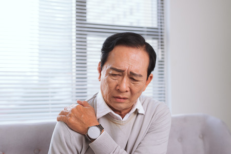 Elderly man suffering from shoulder pain sitting on a sofa in the living room 스톡 콘텐츠