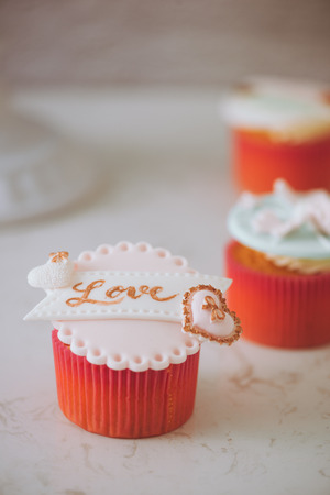 Yummy cupcakes. Valentine sweet love cupcake on table on light background Stok Fotoğraf - 95079631