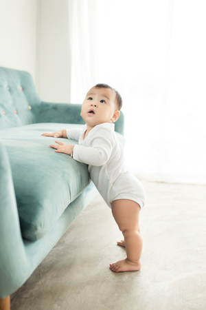 Sweet baby girl standing by the sofa at home. Фото со стока - 95638194