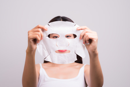 Face skin care. Woman with a cloth moisturizing mask on her face 免版税图像 - 95638361