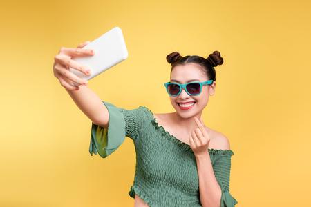Jeune femme asiatique attrayante joyeuse prenant selfies avec sourire.