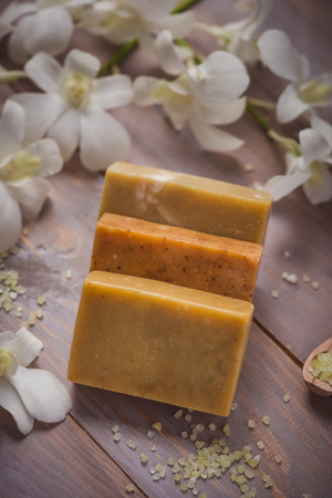 Piece of natural soap with flower on a old wooden table