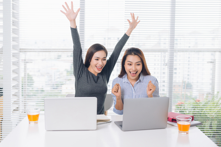 Businesswomen with laptop computer and papers showing thumbs up and celebrating triumph at office Foto de archivo