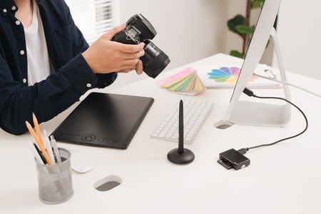 Photographer working at desk in modern office 写真素材