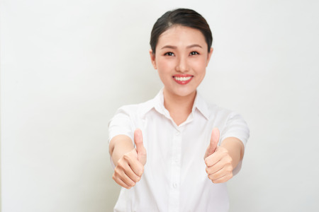 Young asian woman is showing thumb up gesture using both hands.