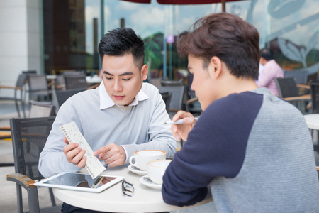 Two young handsome businessmen in casual clothes smiling, discussing in coffee shop. Stock Photo