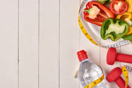 Bell pepper with measuring tape, dumbbells and bottle of water, isolated on white