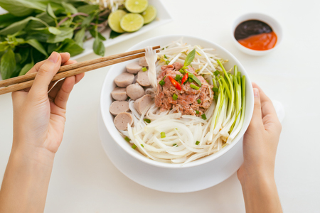 Woman eating traditional Vietnamese Pho noodle using chopsticks. Stock Photo