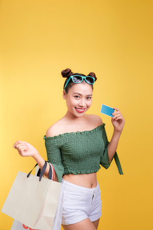 Shopping asian woman holds shopping bags and a credit card on yellow background Stock Photo