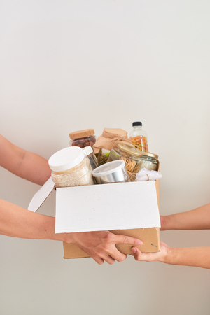 Volunteer with box of food for poor. Donation concept. Stockfoto
