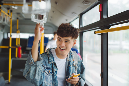 Handsome asian man sitting in city bus and typing a message on the phone. Stock Photo