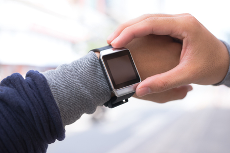 A man using his smart watch app outdoors.