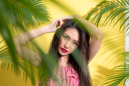 Portrait beauty sexy asian model in summer outfit on palm tree shadow background. 스톡 콘텐츠