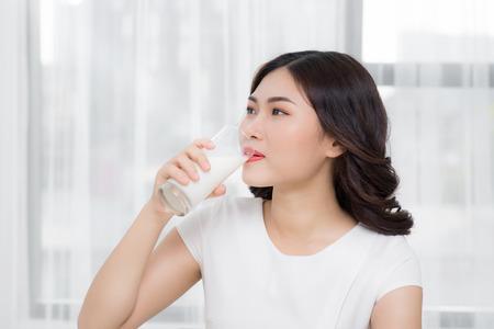 Beautiful asian girl drinking a glass of milk. Standard-Bild