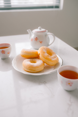sugar donut and tea on white background