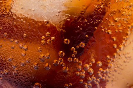 Macro of bubbles and fizz. A cool glass of cola drink with ice