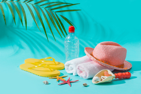 Summer beach vacation and accessories on blue background.