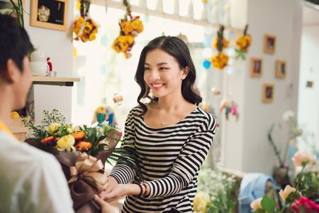 Florist giving bouquet of flower to woman in flower shop Stock fotó