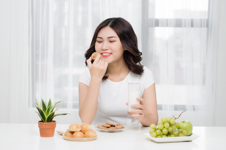 Pretty young asian woman eating tasty cookie at home.