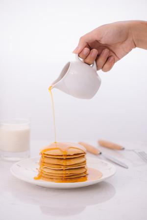 Pfannkuchen zum Frühstück mit Honig und Milch Standard-Bild - 96521249