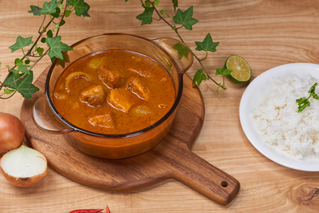 Chicken curry with spice in pot on wooden background