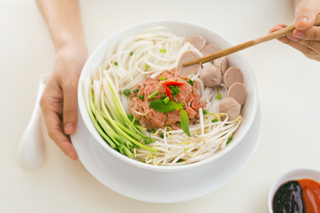 Woman eating traditional Vietnamese Pho noodle using chopsticks. 版權商用圖片