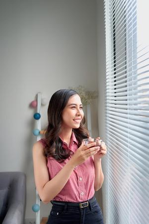 Young woman taking a tea break standing by the office window. Foto de archivo