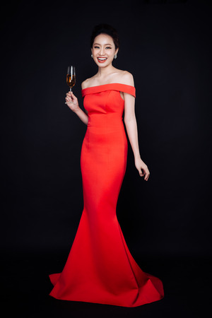 Young asian woman in luxury red dress with glass of sparkling wine. Celebration New Year.