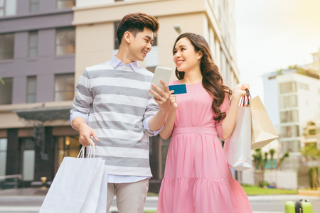 Beautiful asian couple shopping with a credit card in the city
